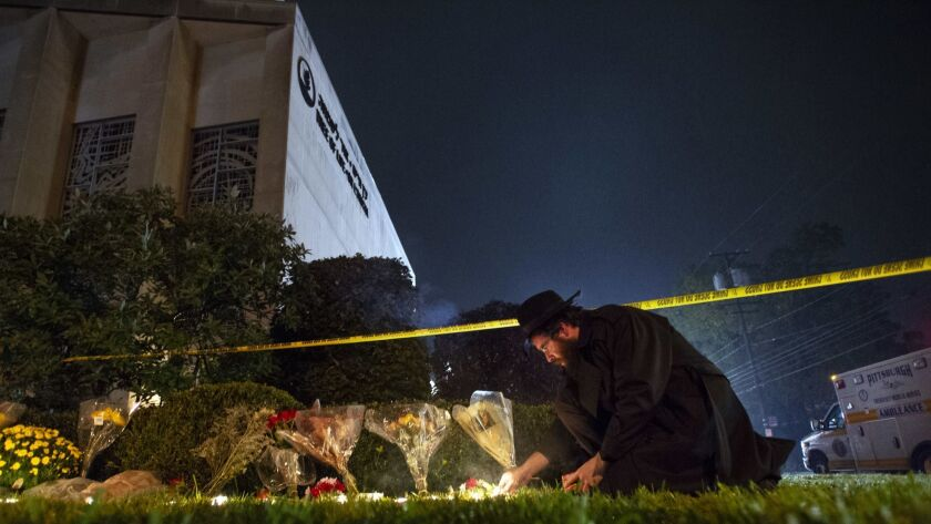 In this Oct. 27, 2018 photo, Rabbi Eli Wilansky lights a candle after a mass shooting at Tree of Lif