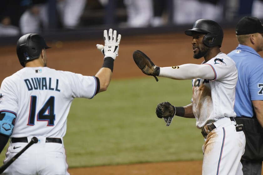 Miami Marlins' Starling Marte, second from right, is congratulated by Adam Duvall (14) after scoring on a single by Garrett Cooper during the third inning of a baseball game against the Los Angeles Dodgers, Monday, July 5, 2021, in Miami. (AP Photo/Wilfredo Lee)