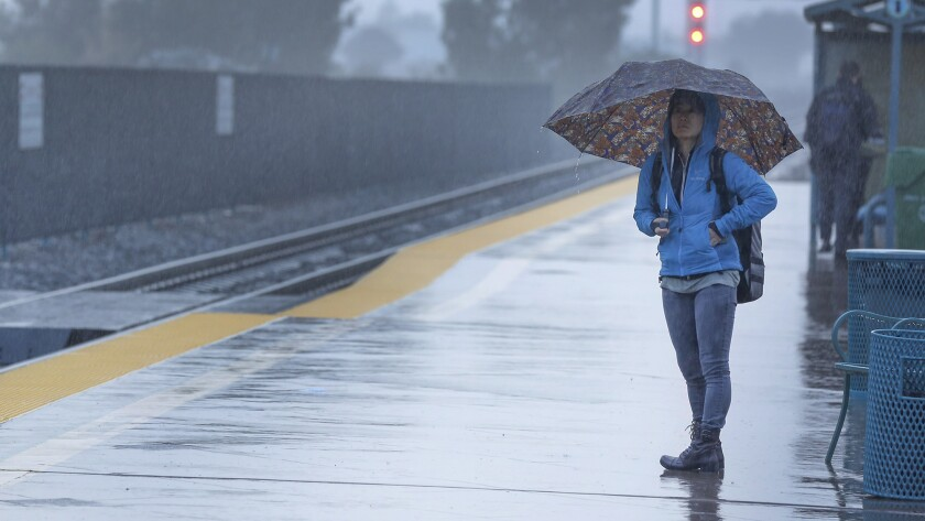 A morning commuter waits in the rain at the Irvine Transportation Center.