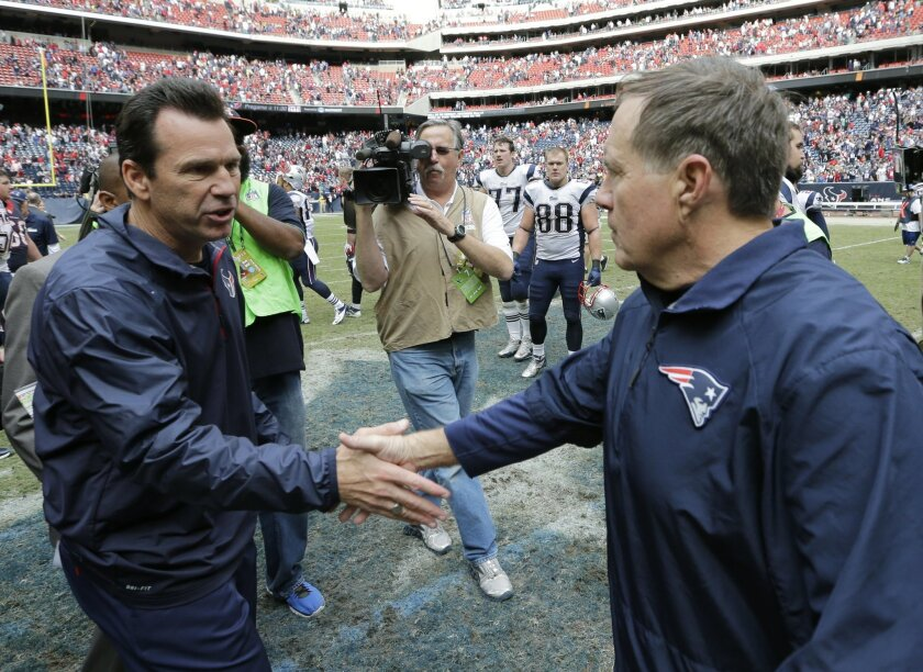 Houston Texans coach Gary Kubiak, left, and New England Patriots coach Bill Belichick, right, shake hands following an NFL football game on Sunday, Dec. 1, 2013, in Houston. (AP Photo/David J. Phillip)