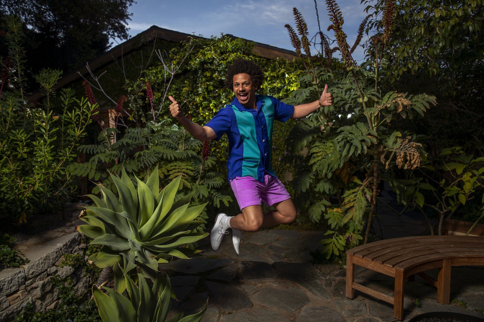 Eric Andre gives double thumbs-up as he jumps in the air