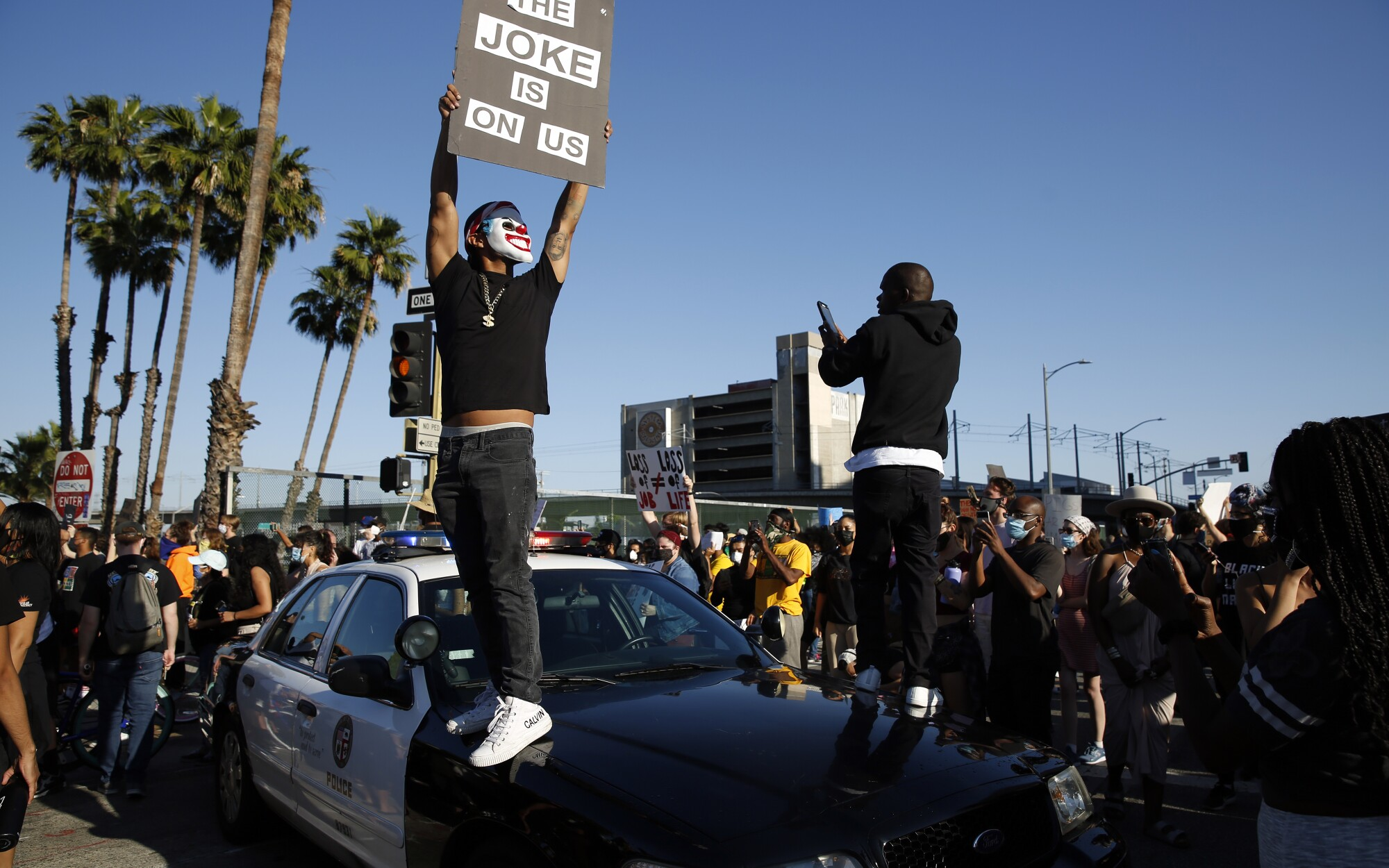 Protesters stand on a LAPD cruiser during a Black Lives Matter protest in downtown Los Angeles