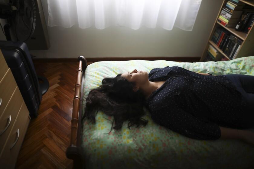 Camila Fernández posa para una foto en su cama durante una cuarentena