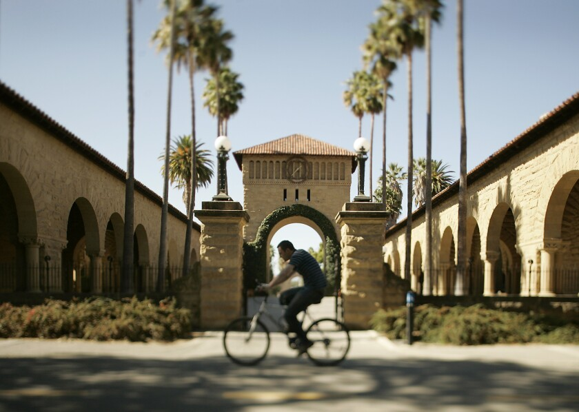 A bicyclist rides on the campus of Stanford University