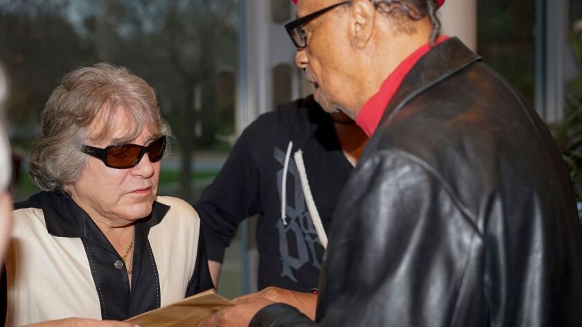 Curtis Long, right, gave José Feliciano the Braille version of a popular Puerto Rican song, pages fr