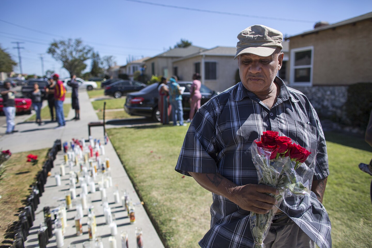 Resident Herbert Baker brings a bouquet of roses to the memorial site for Carnell Snell Jr.