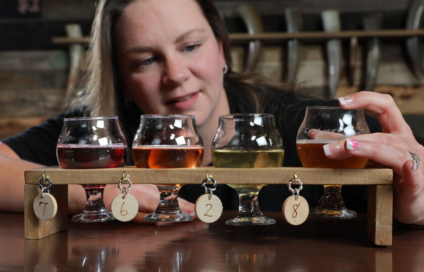 """Katie Fallon, a barmaid here at Twisted Horn Mead & Cider, inspects a just poured """"flight"""" of four samples of the company's products."""