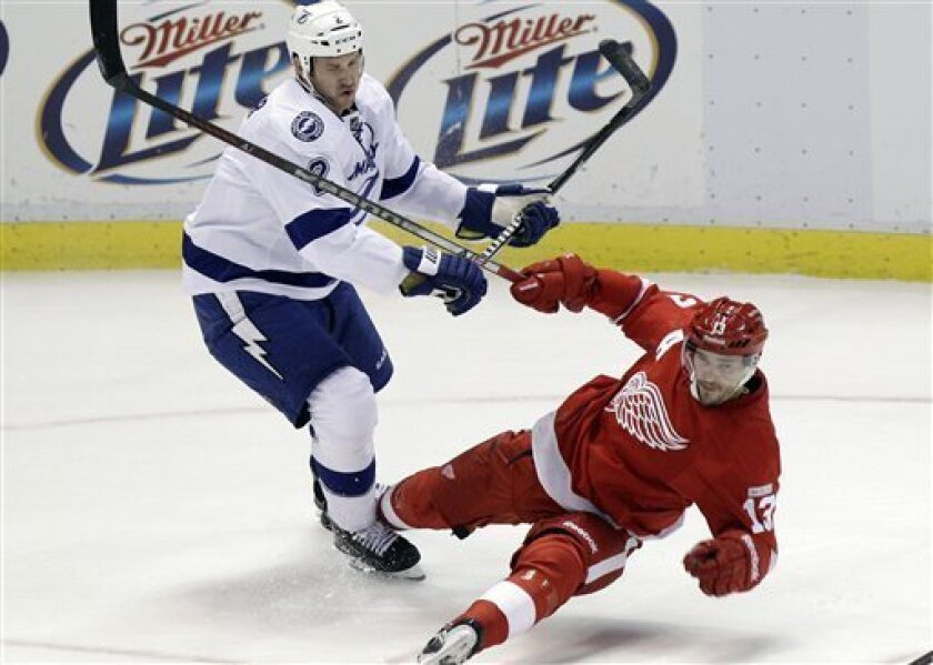 Tampa Bay Lightning defenseman Eric Brewer (2) checks Detroit Red Wings center Pavel Datsyuk (13), of Russia, during the second period of an NHL hockey game in Detroit, Wednesday, Nov. 30, 2011. (AP Photo/Carlos Osorio)