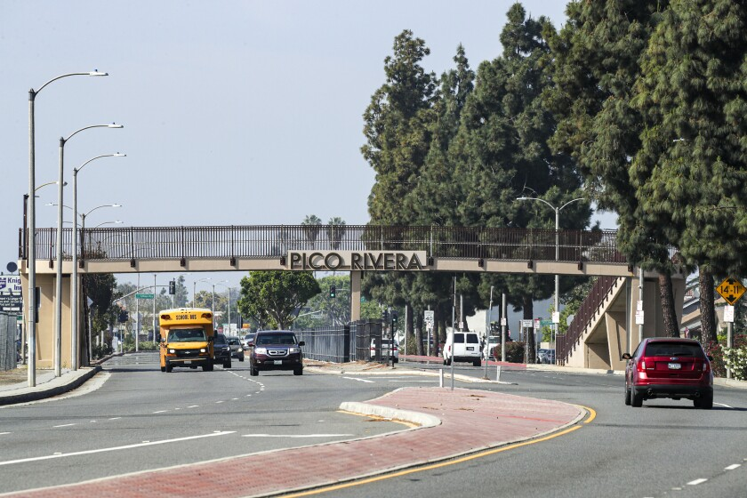 """A road with a pedestrian bridge with the words """"Pico Rivera"""" on it."""