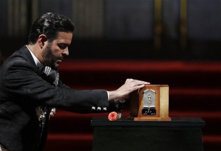 El cantante Pablo Montero toca la urna con las cenizas de Juan Gabriel para decir adiós al superastro de la música mexicana, el lunes 5 de septiembre del 2016 en el Palacio de Bellas Artes, en la Ciudad de México.