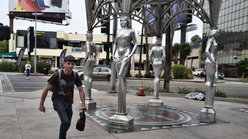"""A skateboarder rides past the """"Four Ladies of Hollywood"""" gazebo on Hollywood Boulevard in Los Angele"""