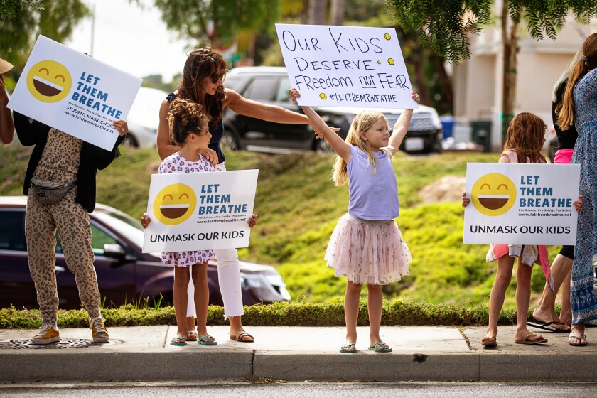 Adults and children with Let Them Breathe, an anti-mask group, protest at the Redondo Beach school district building in July.