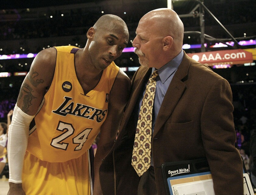 Lakers trainer Gary Vitti checks on a winded Kobe Bryant in a game in March.