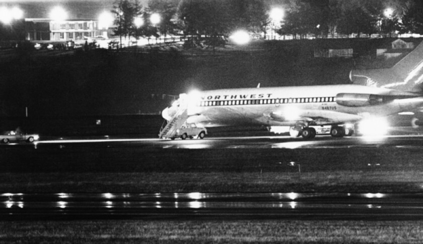 A Northwest Airlines jet, its lights on in the dark, sits on a runway.