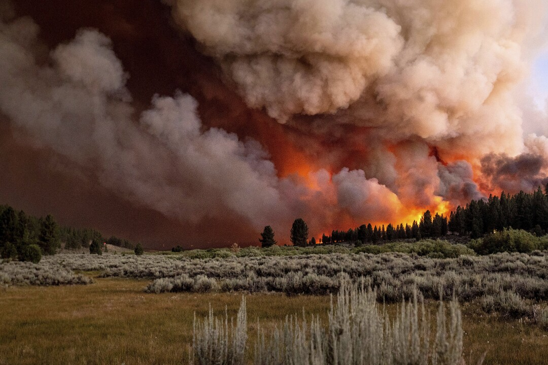 Plumes of smoke and fire rise above Frenchman Lake