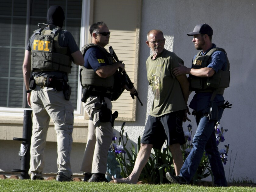 Adelanto Mayor Rich Kerr, second from right, is escorted from his home by FBI officials, Tuesday, Ma