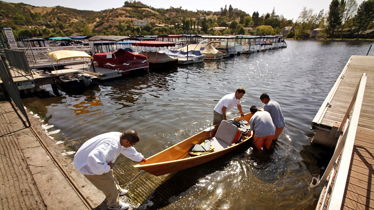 A teacher helps students launch a solar-powered boat in the lake.