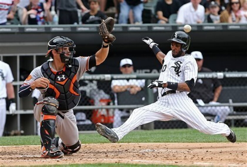 Chicago White Sox' Alexei Ramirez slides into home trying to beat throw and tag by Baltimore Orioles catcher Taylor Teagarden during the sixth inning. Ramirez was safe giving the White Sox a 1-0 lead in a baseball game in Chicago on Thursday, July 4, 2013.(AP Photo/Charles Cherney)