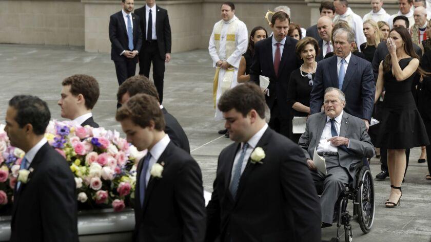 Former President George H.W. Bush and George W. Bush, followed by former first lady Laura Bush follo