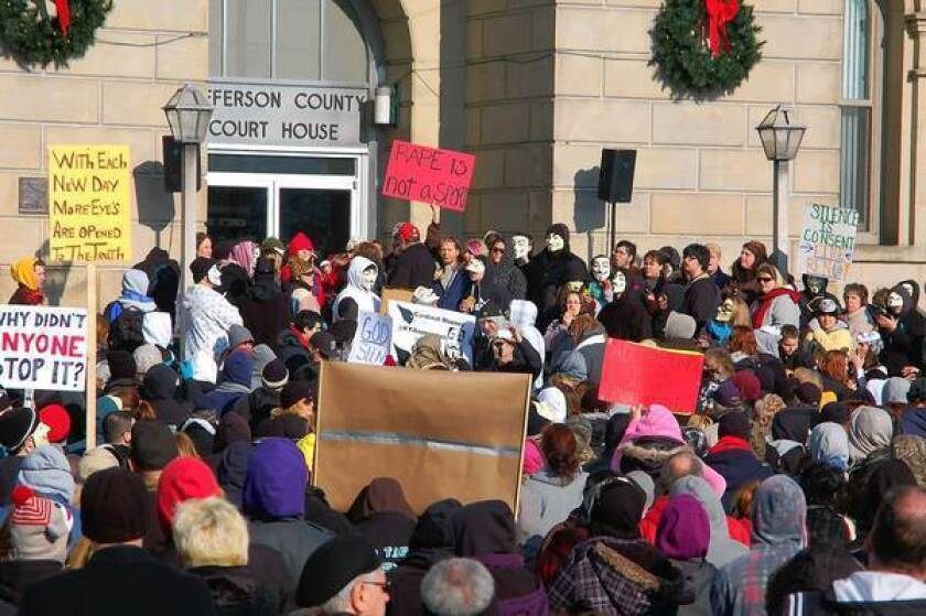 Activists demonstrate at the high school in Steubenville, Ohio, in January. Two members of the football team are about to go on trial on charges of raping a drunken girl while others tweeted and texted videos. The case has sharply divided the town, with some demanding more arrests.