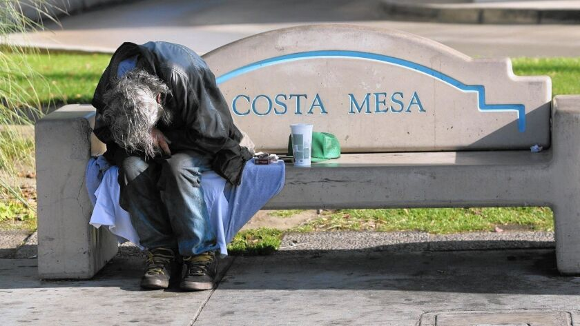 A homeless man sleeps on a bench near Wilson Street and Harbor Boulevard in Costa Mesa. According to