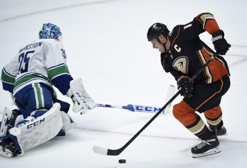 Ducks center Ryan Getzlaf moves the puck around a sliding Canucks goalie Jacob Markstrom for the overtime game-winning goal.