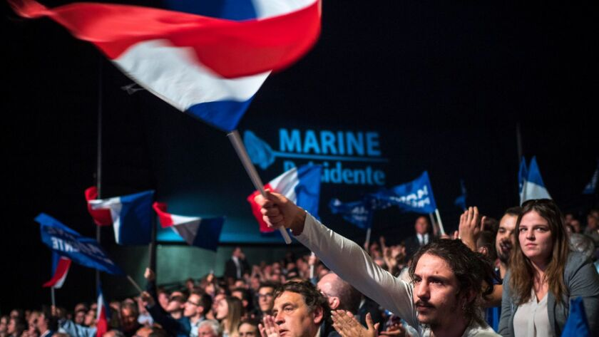 Supporters cheer and wave the French flag as they listen to Marine Le Pen, French National Front political party leader, in Marseille, France, on April 19.
