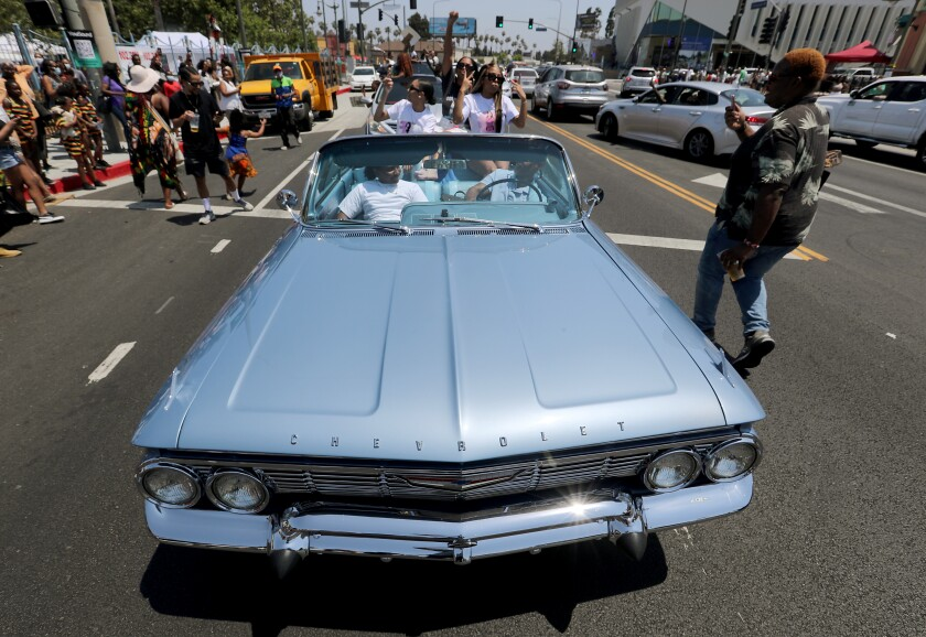 A motorcade of people celebrating Juneteenth makes its way down Crenshaw Boulevard in Leimert Park on Saturday.