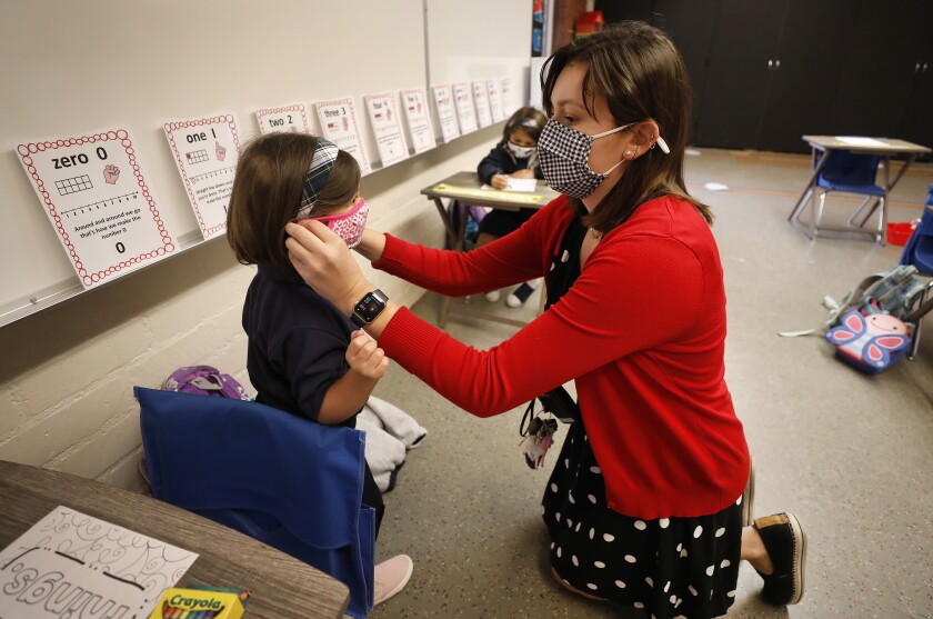 Teacher Heather Hernandez helps a student with her mask