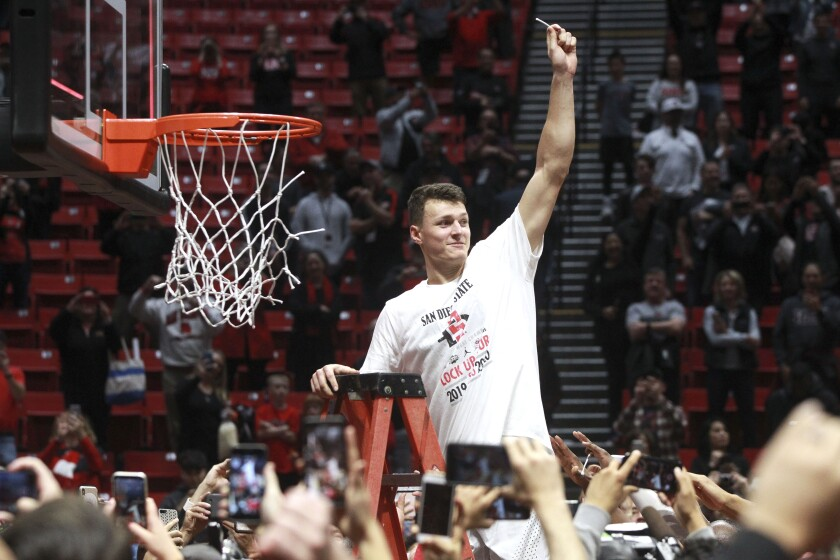 SDSU's Yanni Wetzell celebrates with net cutting after the Aztecs defeated New Mexico at Viejas Arena on Feb. 11.