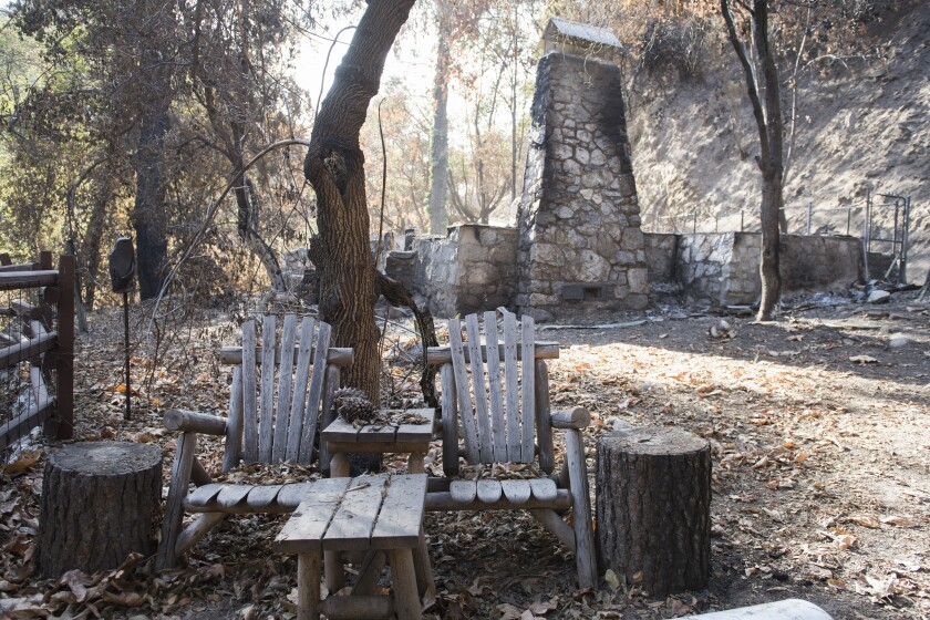 A pair of wooden chairs remain unscathed outside a historic cabin destroyed by the Bobcat fire in Big Santa Anita Canyon.