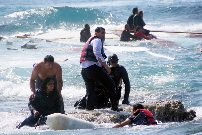 FILE - In this Monday, April 20, 2015 file photo, Greek army Sgt. Antonis Deligiorgis, standing at left, rescues migrant Wegasi Nebiat from Eritrea, front left, from the Aegean sea, on the island of Rhodes, Greece. Deligiorgis was awarded the Cross of Excellency by Defense Minister Panos Kammenos a