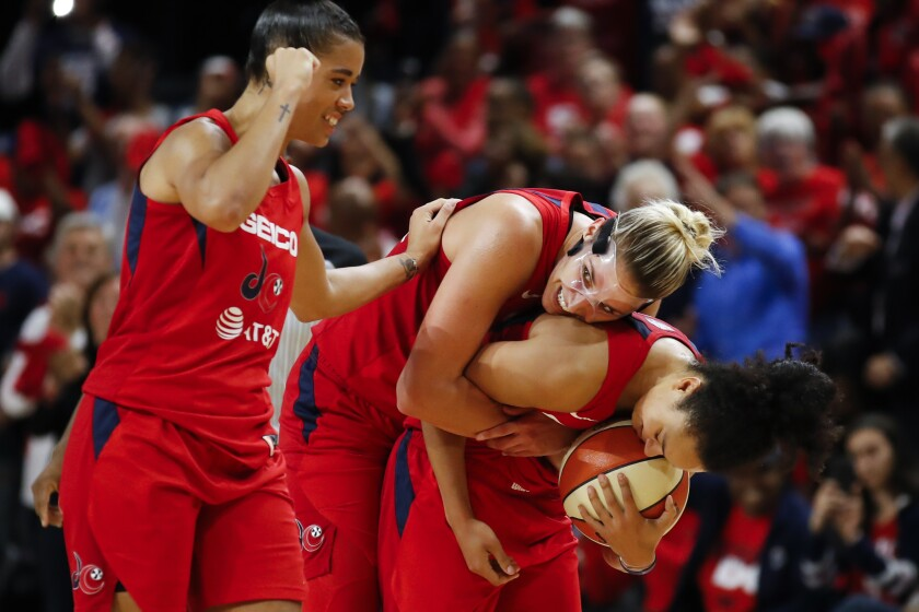 Washington Mystics guard Natasha Cloud, left, forward Elena Delle Donne and guard Kristi Toliver celebrate during the second half of Game 5 of basketball's WNBA Finals, Thursday, Oct. 10, 2019, in Washington. (AP Photo/Alex Brandon)