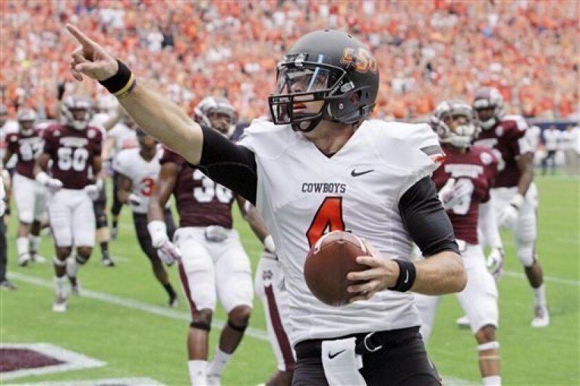 Oklahoma State quarterback J.W. Walsh points to the stands as he scores a touchdown against Mississippi State during the first half of an NCAA college football game,  Saturday, Aug. 31, 2013, in Houston. (AP Photo/Richard Carson)