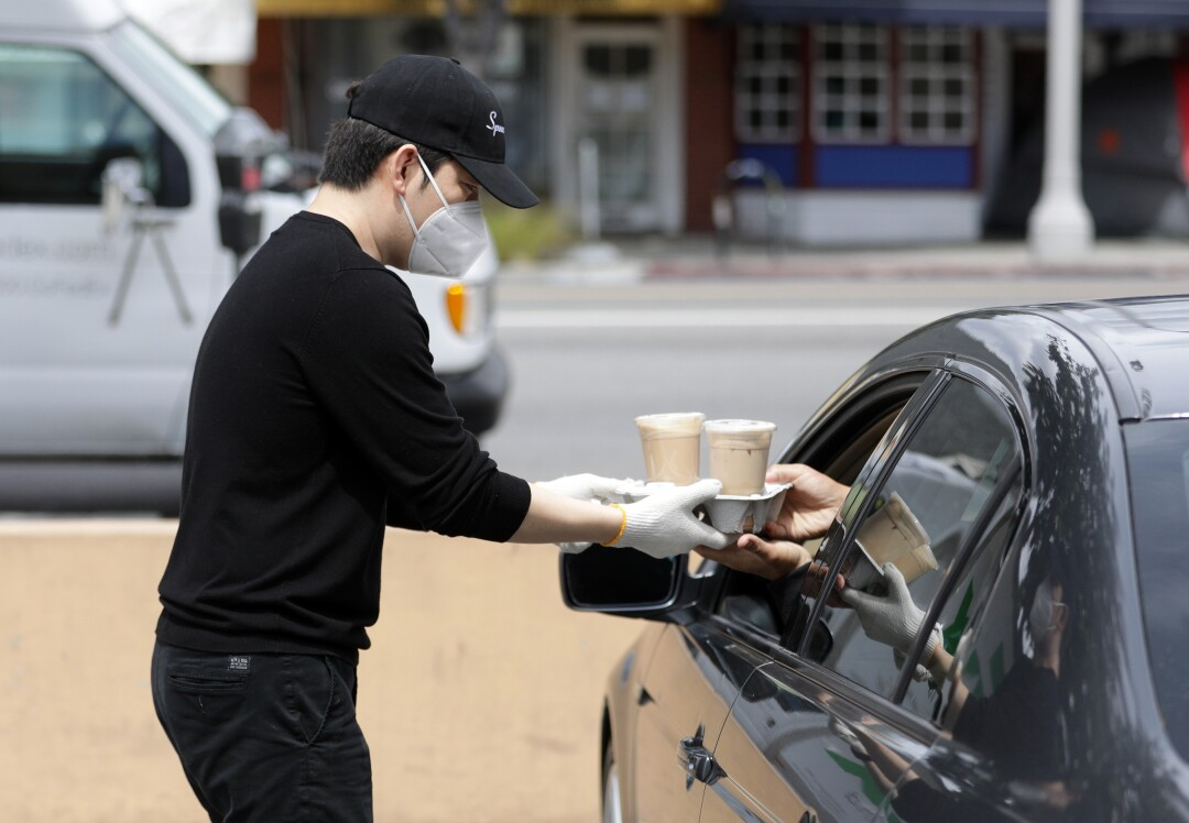 Joseph Hwang, manager of Spoon by H, hands drinks to a waiting customer.