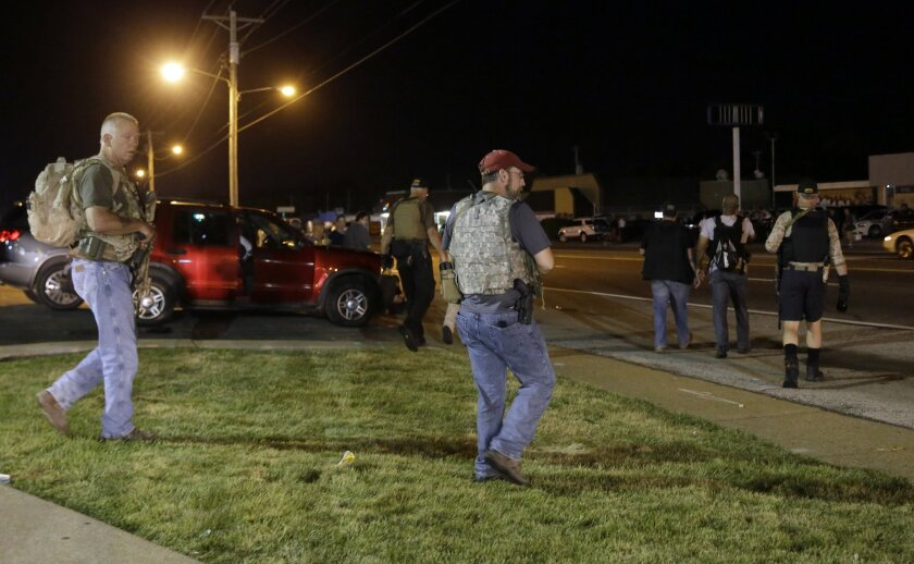 Heavily armed civilians with an anti-government group called the Oath Keepers arrive in Ferguson, Mo., early Tuesday.