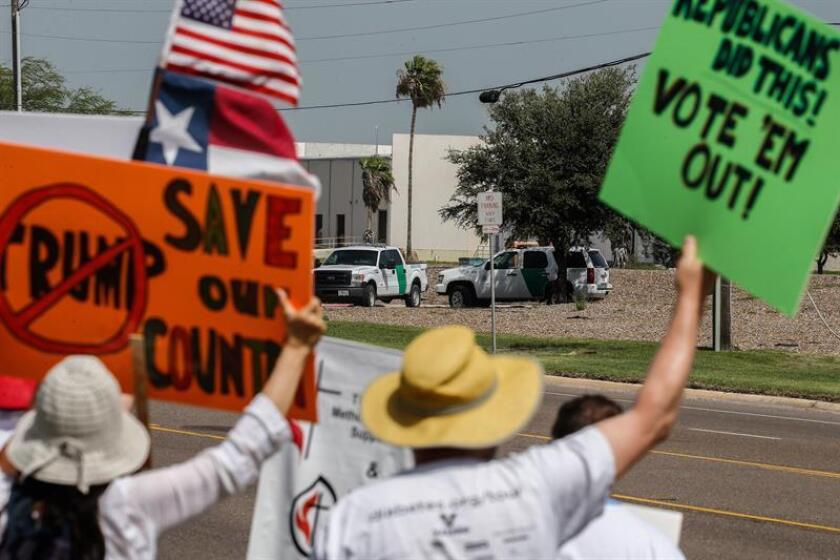 Two Border Patrol vehicles sit across the street from people protesting outside a Border Patrol office during a rally in McAllen, Texas, USA, 30 June 2018. EFE/EPA