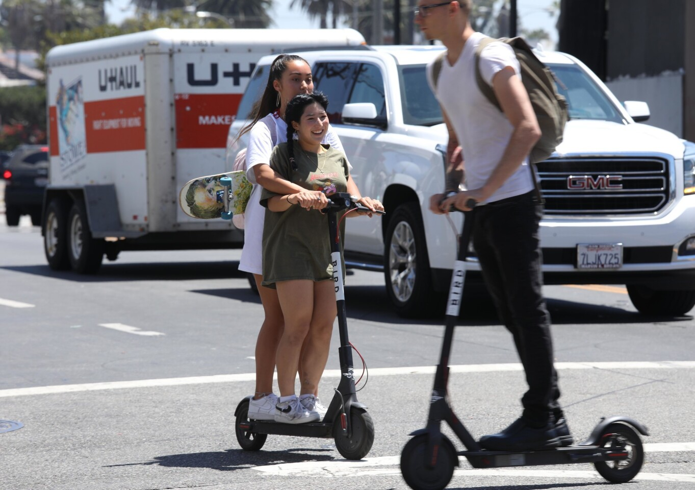 Girls ride across Pacific Avenue on a single Bird scooter as another Bird rider crosses their path in Venice on July 5, 2018. Double riders and riding without helmets are illegal when using the Bird scooter. According to the Bird rental agreement, riders must be 18 years old to operate the scooters.