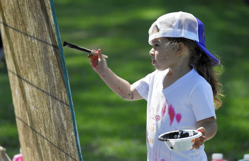 Sienna Lopez, 3, tries her hand at painting during Action Arts in the Park Saturday at TeWinkle Park in Costa Mesa.