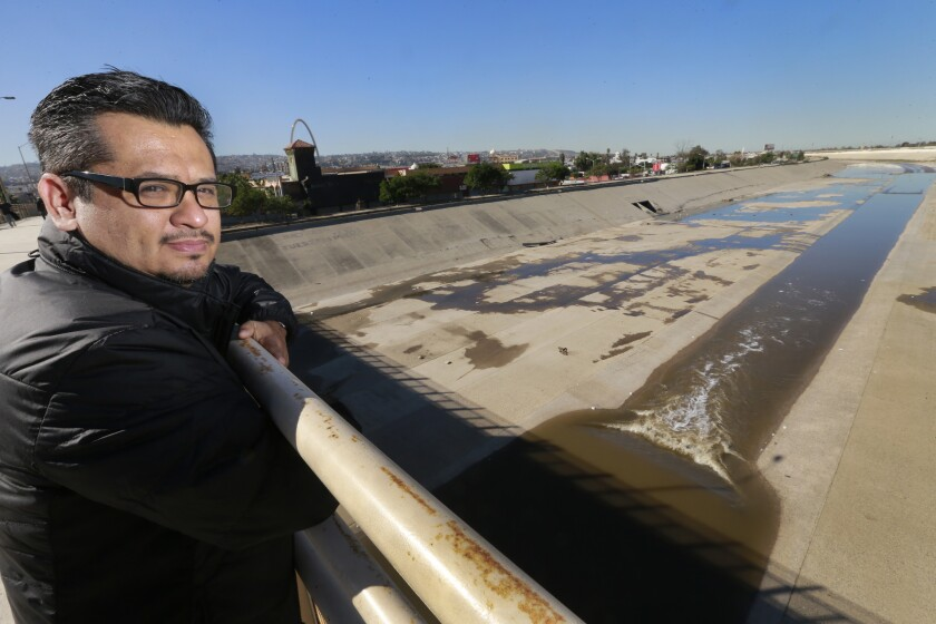 Architect Rene Peralta stands above the Tijuana River. He is proposing a solar farm and green algae cleaning system for the channelized river.