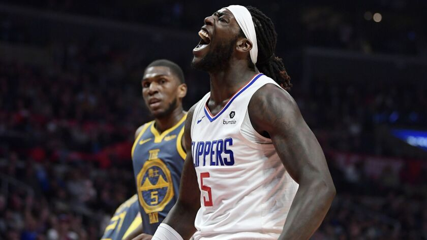 Clippers forward Montrezl Harrell, right, celebrates after scoring as Golden State Warriors forward Kevon Looney watches during the second half.
