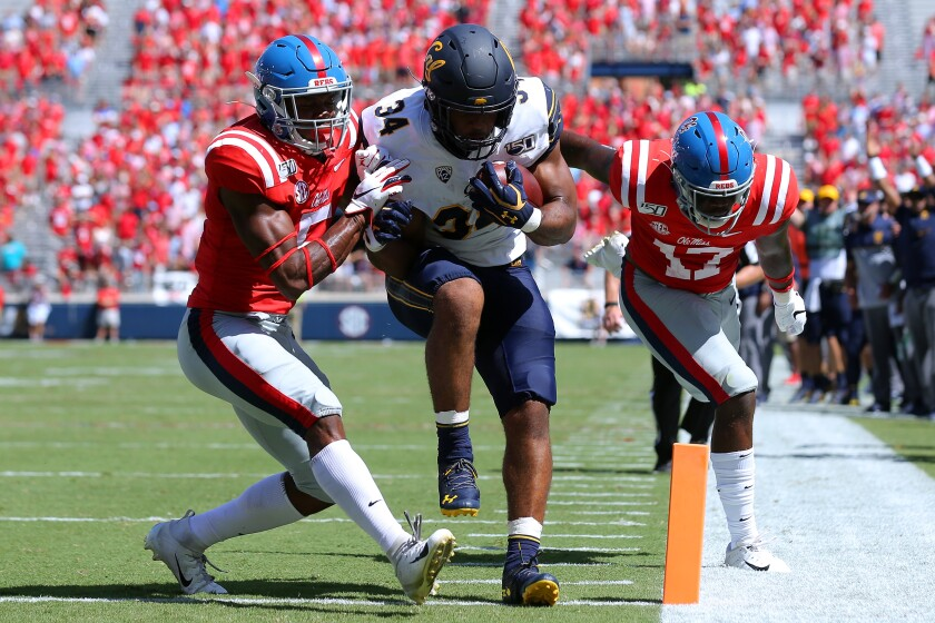 California's Christopher Brown Jr. rushes for a touchdown as Mississippi's Willie Hibbler (17) and Jon Haynes (5) defend during the first half on Saturday in Oxford, Miss.