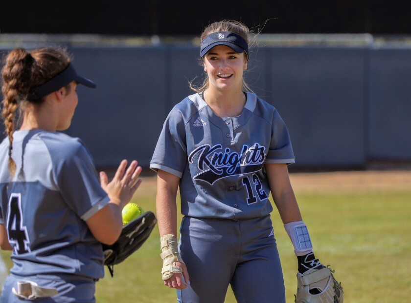 Samantha Turner, at right, of San Marcos, tosses the ball to teammate Sabrina Evans between innings.