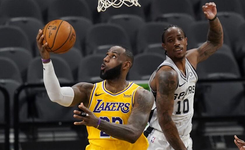 Lakers forward LeBron James scores past San Antonio Spurs guard DeMar DeRozan.