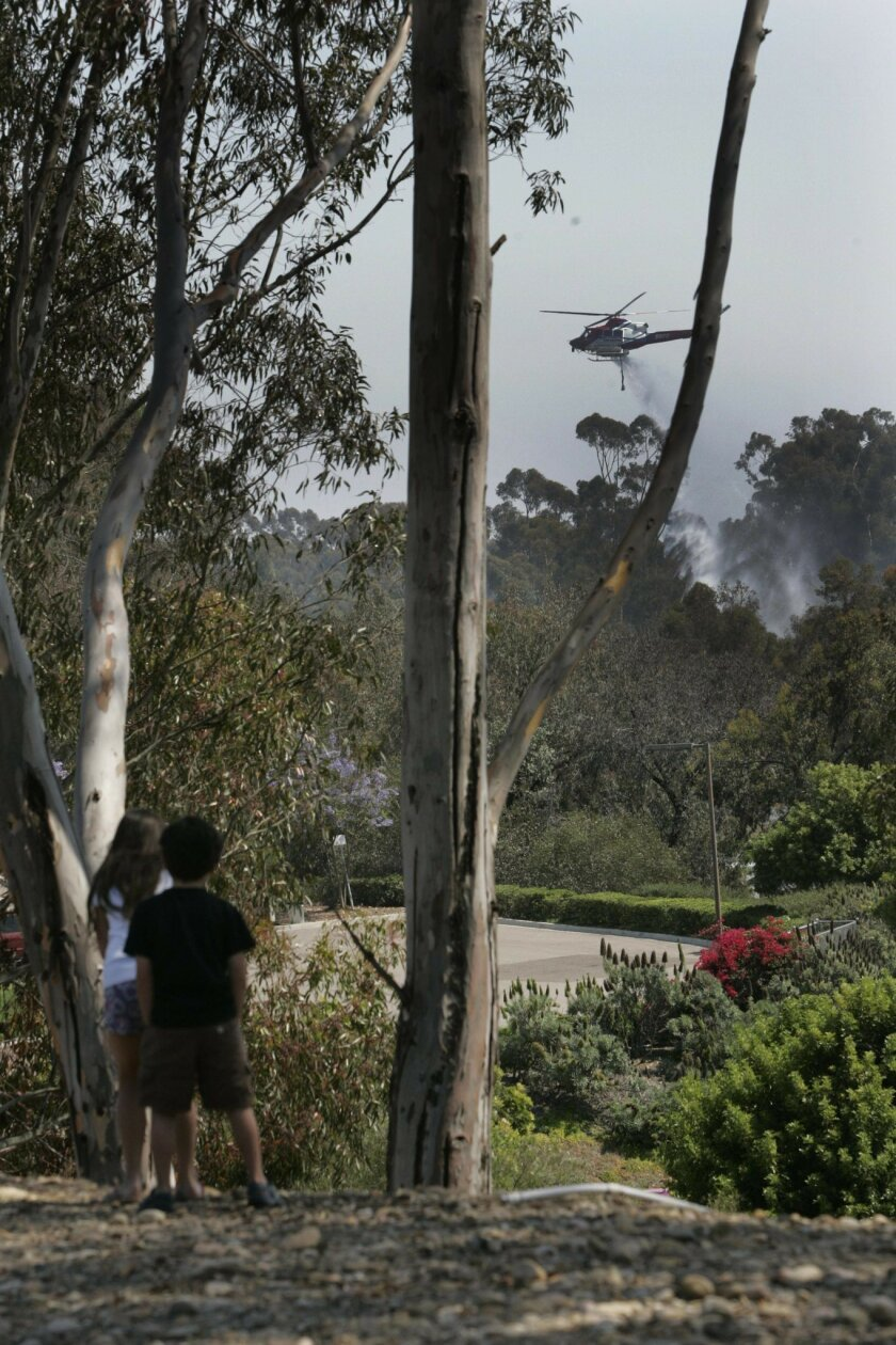 Bystanders watched from behind the Scripps Ranch Libraary as Copter 2 made water drops on the fire.