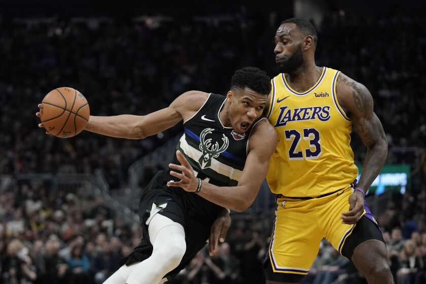 Lakers forward LeBron James (23) tries to cut off a drive by Bucks forward Giannis Antetokounmpo during their game Dec. 19, 2019, in Milwaukee.