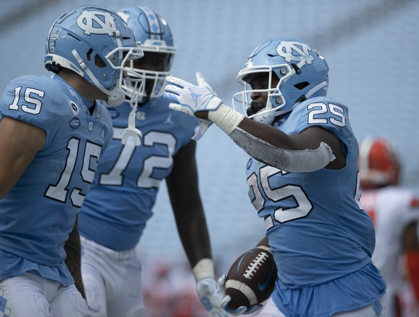 North Carolina's Javonte Williams (25) celebrates with teammates after scoring a touchdown in the fourth quarter of an NCAA college football game against Syracuse on Saturday, Sept. 12, 2020, in Chapel Hill, N.C. (Robert Willett/The News & Observer via AP, Pool)