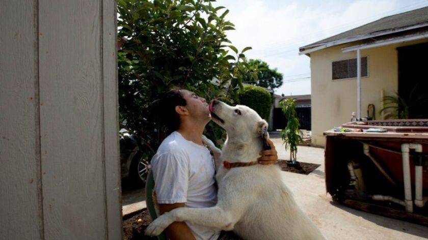 Miguel Delcid, 31, sits in his backyard with his dog on Aug. 6. Delcid grew up in Inglewood. His fat