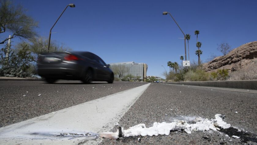 Cars on Monday pass the scene in Tempe, Ariz., where a pedestrian was fatally stuck by an Uber vehicle in autonomous mode.