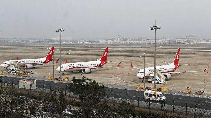 In this photo taken Monday, March 11, 2019, three Shanghai Airlines Boeing 737 Max 8 passenger plane